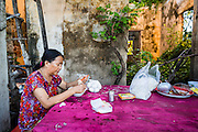 """29 JUNE 2013 - BATTAMBANG, CAMBODIA:  A woman eats at a noodle stand in an old train station on the Phnok Penh - Battambang train line. The station was abandoned during the Cambodian war in the 1970s and never rebuilt. The train line stopped running in the mid 2000s because the tracks were in such disrepair that it wasn't safe to run the trains. Now they are used by """"bamboo trains."""" The bamboo train, called a norry (nori) in Khmer is a 3m-long wood frame, covered lengthwise with slats made of ultra-light bamboo, that rests on two barbell-like bogies, the aft one connected by fan belts to a 6HP gasoline engine. The train runs on tracks originally laid by the French when Cambodia was a French colony. Years of war and neglect have made the tracks unsafe for regular trains.  Cambodians put 10 or 15 people on each one or up to three tonnes of rice and supplies. They cruise at about 15km/h. The Bamboo Train is very popular with tourists and now most of the trains around Battambang will only take tourists, who will pay a lot more than Cambodians can, to ride the train.       PHOTO BY JACK KURTZ"""