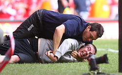 CARDIFF, WALES - SUNDAY, AUGUST 13th, 2006: A steward tackles a fan who ran onto the pitch during the Community Shield match at the Millennium Stadium. (Pic by David Rawcliffe/Propaganda)