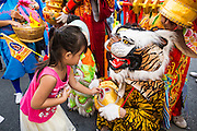24 SEPTEMBER 2014 - BANGKOK, THAILAND: A girl gives a donation to a Chinese Taoist dancer on Yaowarat Road in Bangkok's Chinatown during the Vegetarian Festival Parade. The Vegetarian Festival is celebrated throughout Thailand. It is the Thai version of the The Nine Emperor Gods Festival, a nine-day Taoist celebration beginning on the eve of 9th lunar month of the Chinese calendar. During a period of nine days, those who are participating in the festival dress all in white and abstain from eating meat, poultry, seafood, and dairy products. Vendors and proprietors of restaurants indicate that vegetarian food is for sale by putting a yellow flag out with Thai characters for meatless written on it in red.    PHOTO BY JACK KURTZ