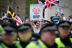 © Licensed to London News Pictures. 01/06/2013. London, UK. A British National Party (BNP) supporter holds up a sign from behind a protective police line after members of Unite Against Fascism broke through a police cordon to confront them during protests by both groups in central London today (01/06/2013). The BNP protest was held in response to the killing of Drummer Lee Rigby, who died after an attack in Woolwich where religious extremism may have been the motive. Photo credit: Matt Cetti-Roberts/LNP