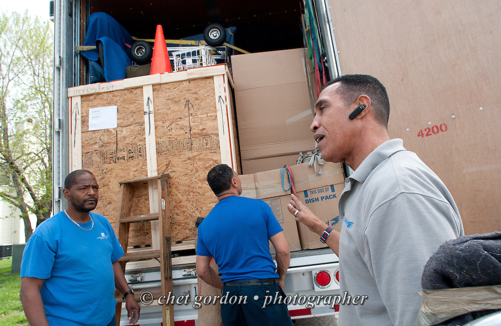 Over the road truck driver Jose Williams (right) directs laborers as they load his trailer outside a shipper's home in Midlothian, VA on Thursday, April 16, 2015. Williams, a cross country trucker with a national household moving company, will make several delivery stops in central California's Bay Area the following week with loads that originated in Virginia.  © Chet Gordon/THE IMAGE WORKS