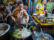 25 OCTOBER 2014 - BANGKOK, THAILAND: A vendor stir fries noodles at a street food stall near Yaowarat Road in Bangkok. Yaowarat Road is the center of the Bangkok Chinatown neighborhood and is famous for the street food. Most of the food stalls open after sunset.     PHOTO BY JACK KURTZ