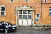 "ROME, ITALY - 30 MARCH 2015: The entrance to the equipment storage of Cinecittà Studios is here in Cinecittà, Rome, Italy, on March 30th 2015.<br /> <br /> Italy instated a special 25% tax credit for film productions in 2010. The industry then lobbied to remove the credit's cap, and last July, Italy lifted its tax credit limit from €5 million per movie to €10 million per company per year. <br />  <br /> Cinecittà, a large film studio in Rome, is considered the hub of Italian cinema. The studios were founded in 1937 by Benito Mussolini as part of a scheme to revive the Italian film industry. In the 1950s, the number of international productions being made here led to Rome being dubbed as the ""Hollywood on the Tiber"". In the 1950s, Cinecittà was the filming location for several large American film productions like Ben-Hur, and then became the studio most closely associated with Federico Fellini.<br /> After a period of near-bankruptcy, the Italian Government privatized Cinecittà in 1997, selling an 80% stake.<br /> <br /> Currently Ben-Hur and Zoolander 2 are booked into Cinecittà Studios."