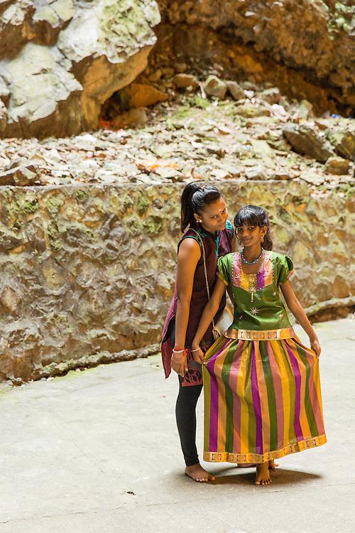 Asia, Malaysia, Kuala Lumpur, Girls pose for snapshots inside shrine at Batu Caves, a Tamil Hindu shrine and tourist attraction
