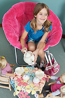 Girl pretending to have tea party with her dolls