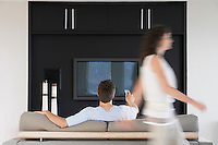 Woman passing by man using remote control in front of flat screen television