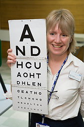 School nurse carrying out eyesight test,