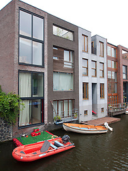 Modern architecture of new houses beside canal on Scheepstimmermanstraat in Borneo Island new property development in Amsterdam Netherlands