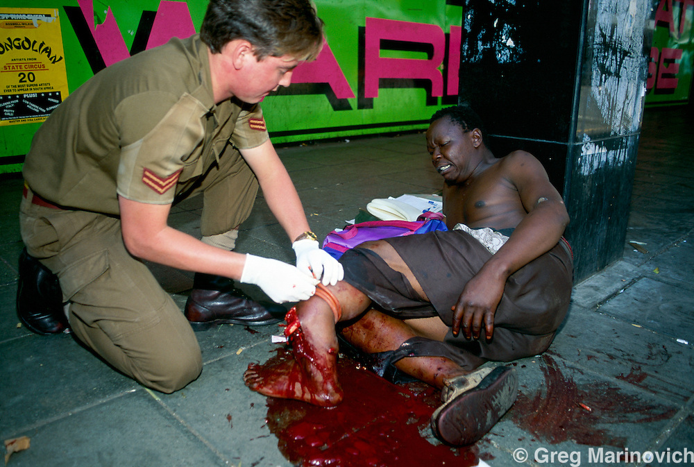 Johannesburg, South Africa, 1994. An army medic treats a man wounded when African National Congress guards opened fire on Inkatha Freedom Party marchers when they approached the ANC headquarters of Shellhouse, Johannesburg 1994. Many IFP supporters killed and wounded. Others were shot from the rooftops by persons unknown at the nearby Library Gardens. Johannesburg, South Africa
