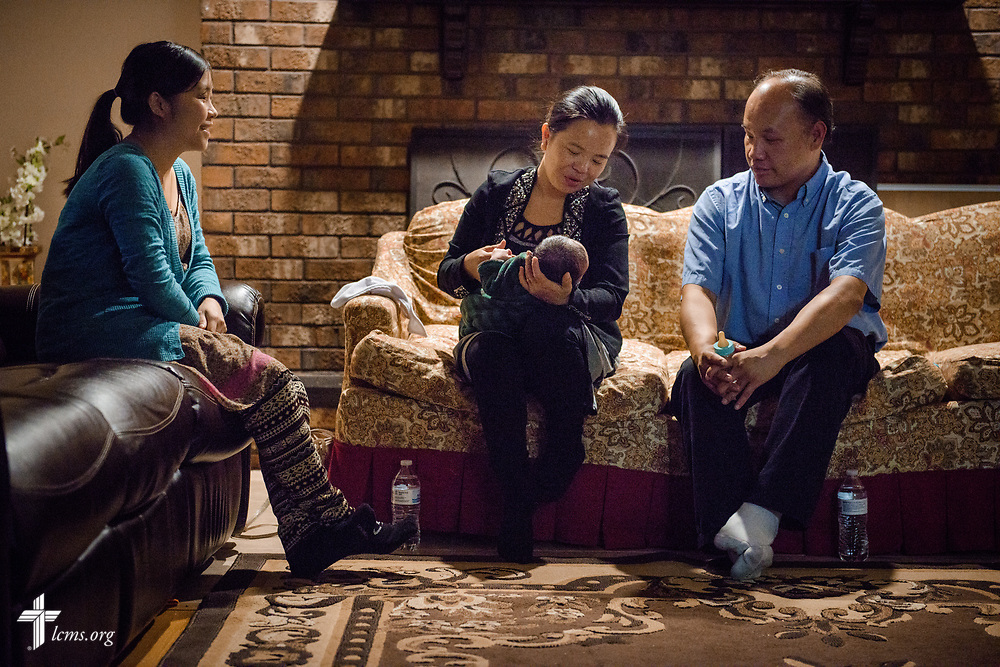 The Rev. Moua Vang (right), associate pastor at Benediction Lutheran Church, Milwaukee, Wis., and his wife Kou, make a home visit with Chuchee Leeyer on Monday, Aug. 14, 2017, in Milwaukee. In this photograph, Kou holds Chuchee's newborn baby boy. LCMS Communications/Erik M. Lunsford