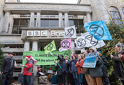 © Licensed to London News Pictures. 21/12/2018. Bristol, UK. 'Extinction Rebellion' campaign event at the BBC Bristol offices in Whiteladies Road where three campaigners locked themselves together blocking the main entrance while others sang modified christmas carols on the shortest day just before Christmas to draw attention to the catastrophic impact of climate change. The Extinction Rebellion campaign says there will be mass actions outside the main BBC headquarters in London, Manchester, Norwich and Bristol to bring to light what they say is the utter failure of the BBC to fulfill their most fundamental duty to educate and inform the British public on the most important issue of our time, the climate crisis.<br /> Extinction Rebellion say the BBC must lead from the front on the climate emergency and make these demands: 1: The BBC Director General Tony Hall to agree to a meeting with a delegation from Extinction Rebellion to discuss how the corporation can meet its crucial moral duty to tell the full truth on the climate and ecological emergency. 2: The BBC to declare a climate and ecological emergency that we need to act now, the extinction of the natural world is happening and we face the collapse of our civilisations.3: That the BBC place the climate and ecological emergency as its top editorial and corporate priority - integrated into all of aspects of the BBC's output, not just environmental sections - by adoption of a climate emergency strategic plan, at the level of urgency the corporation placed on informing the public about World War 2. 4: The BBC to divest all pension funds, investments and bank accounts from fossil fuel corporations and their bankers. 5: The BBC, its subsidiaries and its supply chain to agree to be zero-carbon by 2025. 6: The BBC to publish an annual eco-audit of all BBC operations, including summary of key ecological and carbon data. 7: The BBC to take a lead on encouraging other national & global media corporations to join the global ef