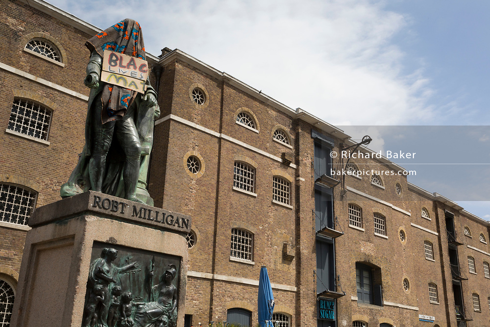 Hours before it was removed by its owner, the Canal and River Trust charity, the statue of slave merchant, Robert Milligan stands covered by Black Lives Matter activists outside the Museum of London's Docklands Museum on West India Quay, once the world's longest warehouse paid for by slavery profits, on 9th June 2020, in London, England. In the aftermath of the George Floyd protests in the US and UK Black Lives Matter groups, who are calling for the removal of statues and street names with links to the slave trade, Milligan's and other statues of British slavery profiteers, have become a focus of protest.