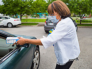 21 MAY 2020 - DES MOINES, IOWA: A volunteer at an emergency food distribution in Evelyn K. Davis Park in central Des Moines, hands a box of Girl Scout cookies to people in a car. All of the 485 meals were distributed in about an hour. The economic fallout of the pandemic is being felt throughout Iowa. On May 21, 2020, Iowa reported that 187,375 people had filed for unemployment since the beginning of the COVID-19 pandemic and resulting economic shutdown. Emergency food pantry has also increased in that time, as many Iowans in low wage jobs used emergency food banks and pantries for the first time. The Food Bank of Iowa said Thursday that demand in April 2020 was 31% higher than demand in April 2019, mostly because of unemployment caused by the Coronavirus (SARS-CoV-2) pandemic. The emergency food distribution Thursday was organized by the city of Des Moines, Food Bank of Iowa, Central Iowa Shelter and Services, Urban Dreams and Orchestrate Hospitality.     PHOTO BY JACK KURTZ