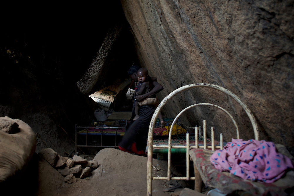 A Nuba family takes cover, from possible bombardments by Sudan's Army Forces airplane, in some caves near Buram village.