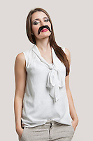 Portrait of beautiful young woman with fake mustache against gray background