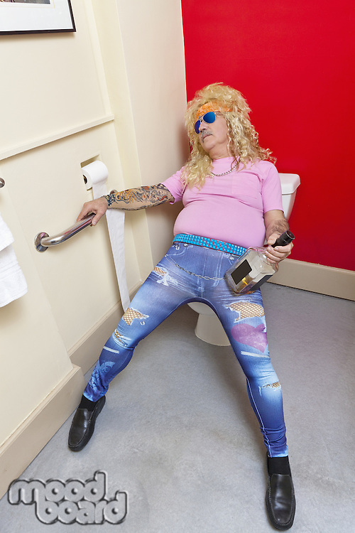Drunk man sitting on toilet seat