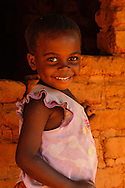 a young girl smiling in fron of a red brick house near Nkhata bay, malawi