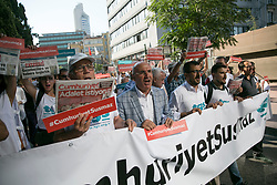 "Journalists and people hold a banner reading ""Cumhuriyet won't be silenced"" and copies of Cumhuriyet opposition daily reading ""We want Justice"" as they march to the courthouse from Cumhuriyet daily's headquarters on July 24, 2017 in Istanbul, Turkey. Photo by Tolga Sezgin/NARphotos/ABACAPRESS.COM"