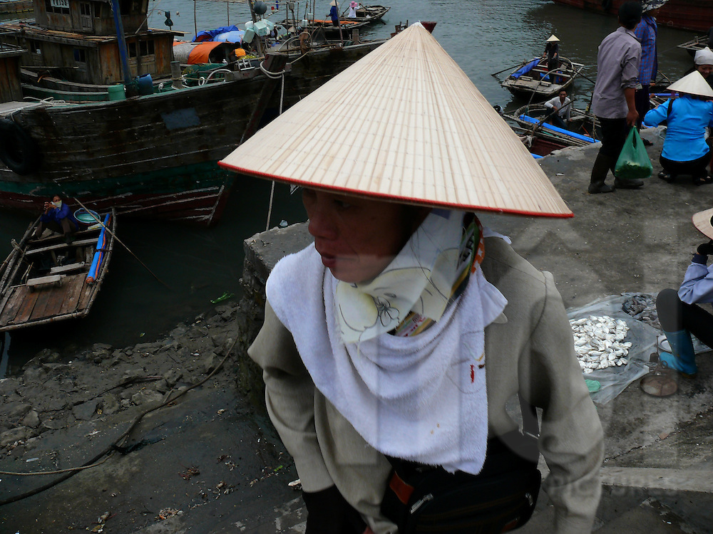 Woman wearing a conical hat hangs out at a fish market on Van Don Island in Bai Tu Long Bay, Vietnam, Southeast Asia