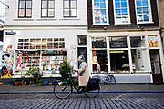In Dordrecht rijdt een oudere vrouw op de fiets door de historische binnenstad langs een stripwinkel<br /> <br /> In Dordrecht a cyclist rides at the historical city center.