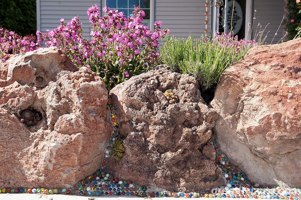 Artist Will Bennett's landscaping incorporates marbles for both asthetics purposes and practical purposes as a weed barrier. <br />