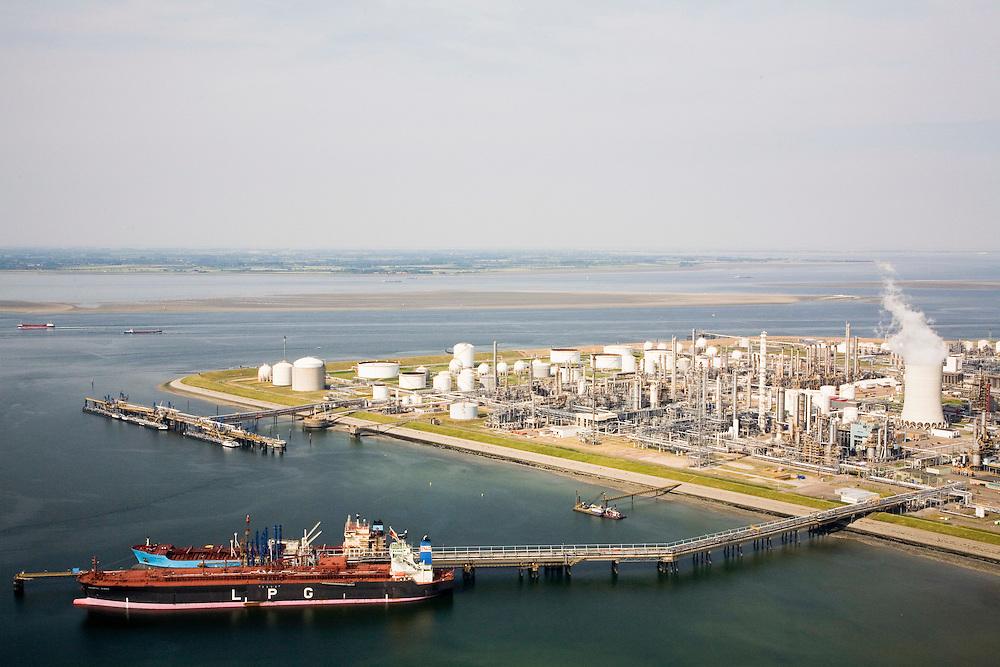 Nederland, Zeeland, Terneuzen, 04-07-2006;  site van de chemische fabriek van Dow (Dow ChemicaCompany) aan de Westerschelde; in de voorgrond afgemeerde tanker voor LPG, een van de grondstoffen; in de achtergrond de Westerschelde met de het zand van de Middelplaat (daarvoor schepen in de vaargeeuvan de Pas van Terneuzen) .de kraakinstallaties maken o.a. benzeen, ethyleen en propyleen (deze basischemicaliÎn worden verwerkt tot verschillende halffabrikaten die weer de bouwstenen voor verschillende kunststoffen vormen. .Site of the chemicaplant of Dow ChemicaCompany. This plant produces benzene, ethylene and propylene, the basis for various plastics.  luchtfoto (toeslag); aerial photo (additional fee required); .foto Siebe Swart / photo Siebe Swart