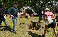 Bill Shea invites Pauline Wood of Goffstown to taste the beef stew cooked over the open fire during the 5th NH Volunteers Civil War encampment set up during Sanbornton Old Home Day on Saturday.  (Karen Bobotas/for the Concord Monitor)