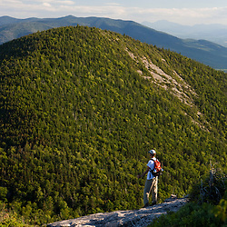 A hiker on the Cohos Trail near the summit of North Percy Peak.  Nash Stream State Forest, Stratford, New Hampshire.  South Percy Peak is in the distance.