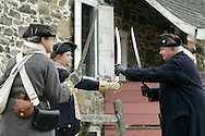 Newburgh, New York - Revolutionary War reenactors in uniforms drill with swords at Washington's Headquarters State Historic Site as part of George Washington's birthday celebration on Feb. 18, 2012. The reenactors are from John Lamb's Artillery Company. Hasbrouck House, the longest-serving headquarters of Washington during the American Revolution, is in the background.
