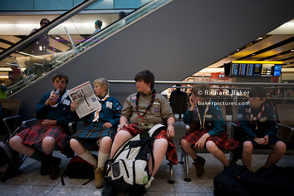 Wearing kilts, boys from a Scottish scout group sit and in the departures concourse of Heathrow Airport's Terminal 5.