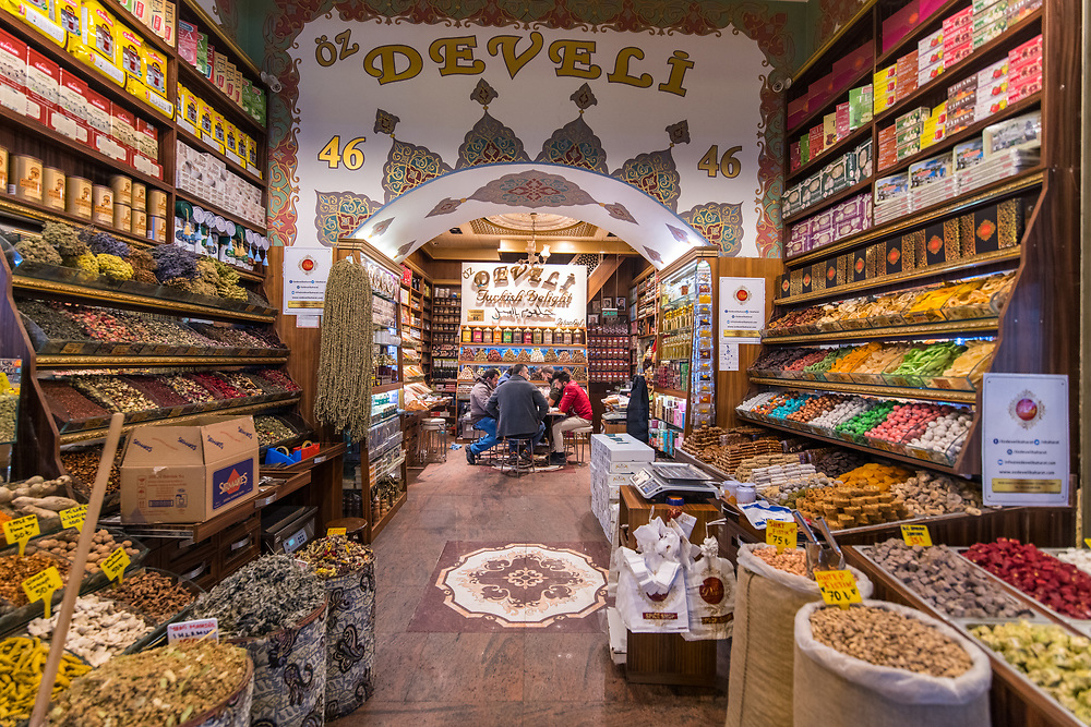Inside spice store at Istanbul Spice bazaar in Turkey with a group of men sitting and conversing around small table.