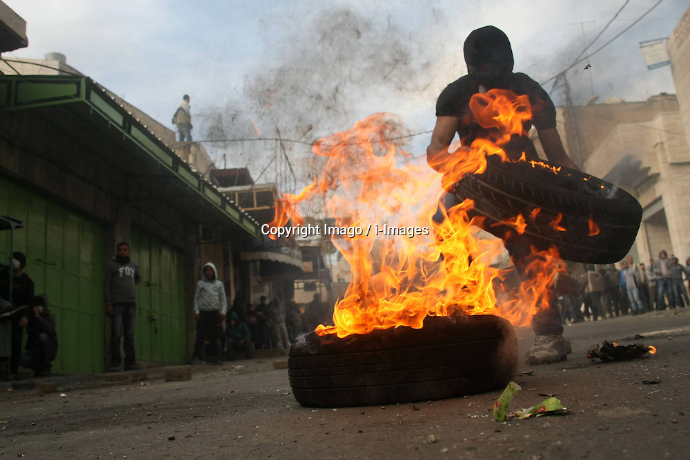 A Palestinian protester burns tires during clashes with Israeli soldiers in the West Bank city of Hebron, February 25, 2013. Photo by Imago / i-Images...UK ONLY