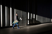 A man carries an ironing board while passing through a shaft of sunlight, on 7th February 2018, in London, England.