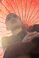A young novice monk with a red parasol.