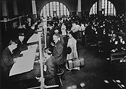 Interpreters sitting next to the immigrants while immigration officers examine their documents, in the Registry Room, photograph, c. 1912, displayed in the Ellis Island Immigration Museum, in the main building on Ellis Island, the immigration processing centre for the United States from 1892 to 1954, at the mouth of the Hudson river in New York City, NY, USA. Ellis Island and its Immigration Museum are part of the Statue of Liberty National Monument and are managed by the National Park Authority. Picture by Manuel Cohen