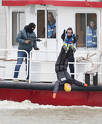 © Licensed to London News Pictures.19/03/2017.London, UK. A man carrying a gun and wearing a balaclava acting the part of a terrorist watches as police simulate a body being thrown off a cruise boat during an ant-terrorist training exercise on The River Thames in London. It is the first time that an exercise of this type has taken place on the river.Photo credit: Peter Macdiarmid/LNP