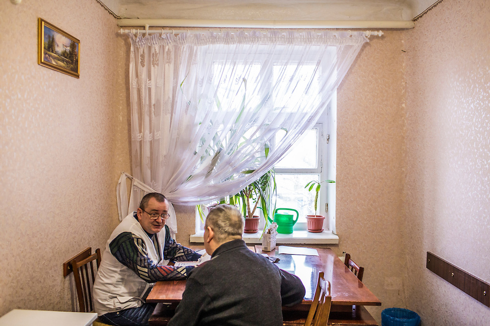 ZIMOGORYE, UKRAINE - MARCH 15, 2015: Andriy Polyakov, left, a doctor with Medecins Sans Frontieres, consults with a patient at the Zimogoryivskaya Ambulatory in Zimogorye, Ukraine. CREDIT: Brendan Hoffman for The New York Times
