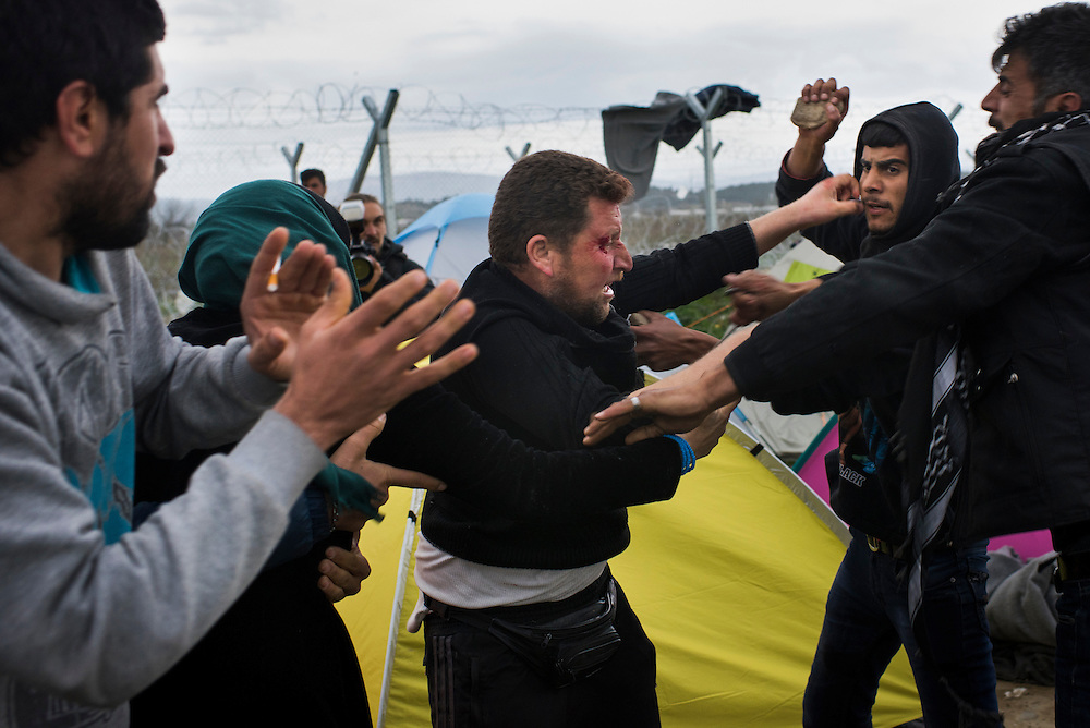 Refugees fight using rocks and fists at a camp on the Macedonian (FYROM) border (seen in the background) on March 7, 2016 in Idomeni, Greece. The fight over living space broke out as migrants waited for EU Leaders to make a decision on the Balkan refugee route.