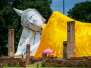 17 JULY 2017 - INTHA PRAMUN, ANG THONG, THAILAND: The reclining Buddha at Wat Khun Inthapramun. Wat Khun Inthapramun houses the largest and longest reclining Buddha in Thailand. The statue of the reclining Buddha is more than 50 meters long. The temple is located in the middle of rice fields, in the southern part of the Pho Thong district. The temple was built during the Sukhothai era, is revered in Thai history and late King Bhumibol Adulyadej (Rama IX) visited twice, in 1973 and 1975.    PHOTO BY JACK KURTZ
