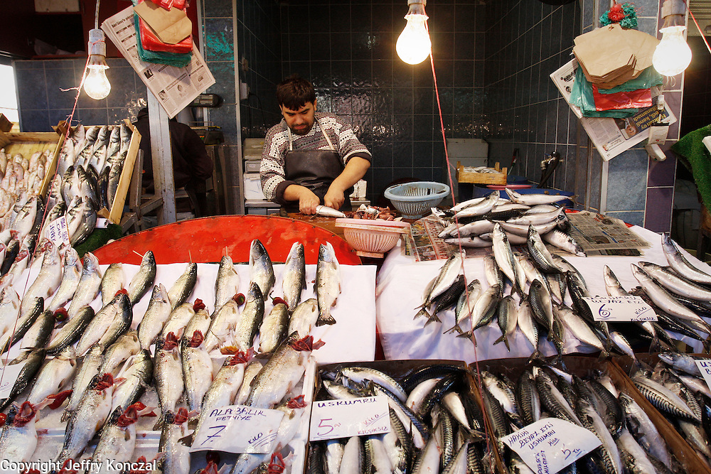 A man prepares fish at a open air market in Izmir, Turkey