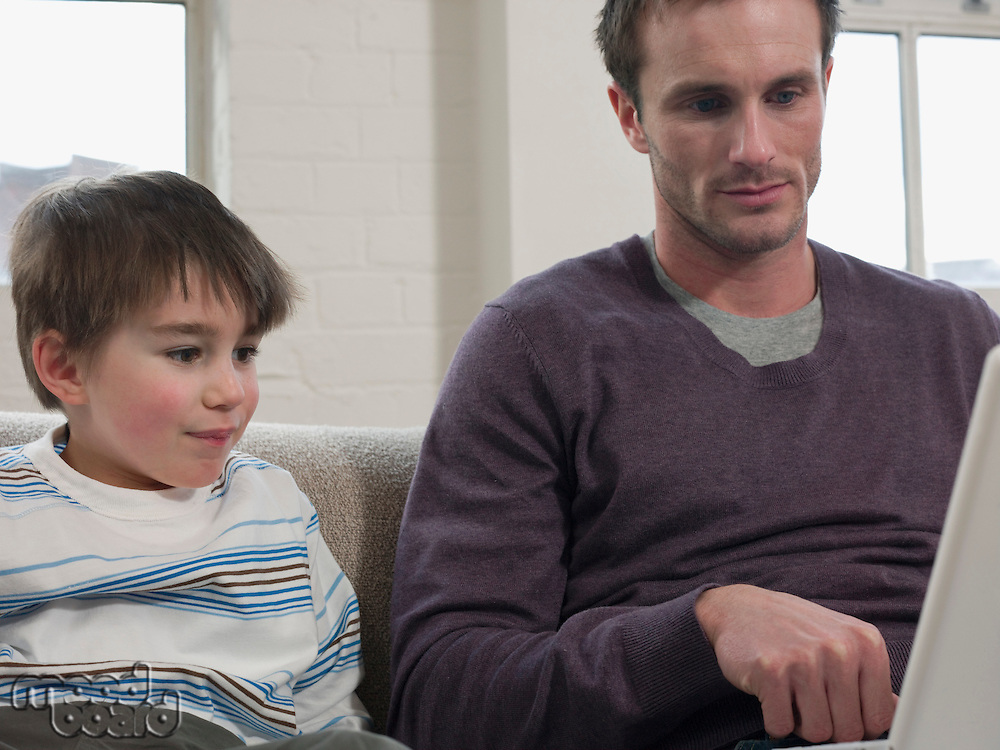 Son Watching Father Use Laptop