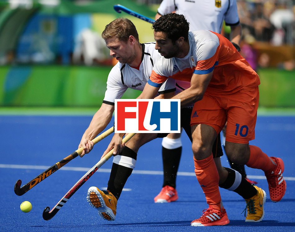 Germany's Martin Haner (L) vies with Netherlands' Valentin Verga during the men's Bronze medal field hockey Netherlands vs Germany match of the Rio 2016 Olympics Games at the Olympic Hockey Centre in Rio de Janeiro on August 18, 2016. / AFP / Pascal GUYOT        (Photo credit should read PASCAL GUYOT/AFP/Getty Images)