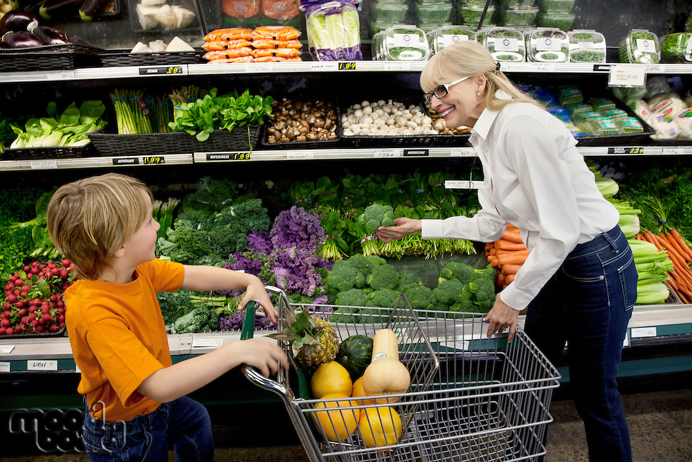 Happy woman selecting vegetable while boy with shopping cart looking in grocery market