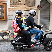 Mother, father and child riding a Vespa motorscooter, Corso Ruggero, Cefalu, Sicily, Italy