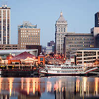 Picture of Peoria Illinois skyline with downtown city buildings along the Illinois River and the Spirit of Peoria paddlewheel riverboat.