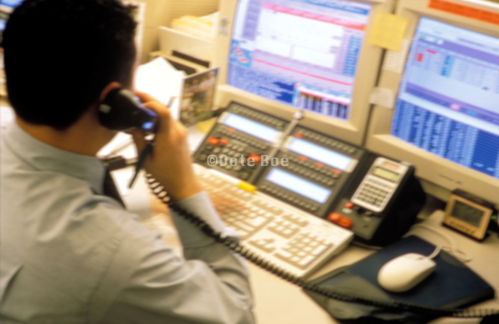 office worker on the phone while watching the computer screens and typing.