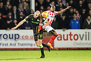 Forest Green Rovers Farrend Rawson(6) heads the ball clear under pressure from Cheltenham Town's Adam Page(16) during the EFL Sky Bet League 2 match between Cheltenham Town and Forest Green Rovers at Jonny Rocks Stadium, Cheltenham, England on 29 December 2018.