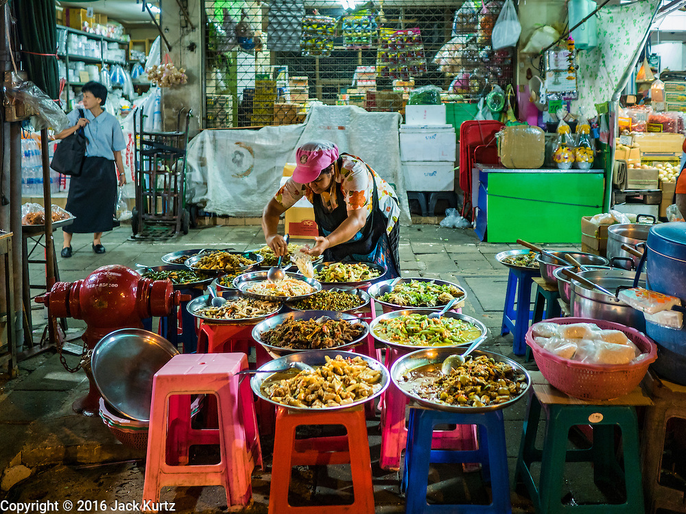 24 FEBRUARY 2016 - BANGKOK, THAILAND:  A street food vendor serves an order of curry in her stall on the sidewalk in front of Pak Khlong Talat in Bangkok. Bangkok government officials announced this week that vendors in Pak Khlong Talat, Bangkok's well known flower market, don't have to move out on February 28. City officials are trying to clear Bangkok's congested sidewalks and they've cracked down on sidewalk vendors. Several popular sidewalk markets have been closed in recent months and the sidewalk vendors at the flower market had been told they would be evicted at the end of the month but after meeting with vendors and other stake holders city officials relented and said vendors could remain but under stricter guidelines regarding sales hours. The flower market is one of the best known markets in Bangkok and has become a popular tourist destination.       PHOTO BY JACK KURTZ