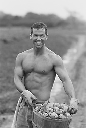 shirtless man smiling while holding a basket of fresh picked potatoes