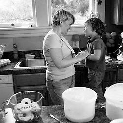 """Vera Wilson (left) communicates with her son, Eli (right, age 3), as they make pies in their kitchen. Eli, who has profound hearing loss, needs hearing aids and insurance will not cover them. Vera hopes to make and sell 1000 pies to help offset cost of Eli's hearing aids. """"I was supposed to have a charmed life. I guess this has caused me more spiritual; trust more. My mother died shortly after Eli was diagnosed. I could hear her looking down and saying 'It's going to be fine'. With the help of my church and the HANDS hearing support group, I know we will make it."""""""